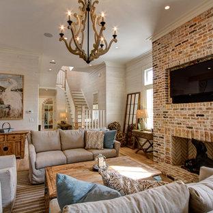 マイアミの巨大なビーチスタイルのおしゃれなファミリールーム (白い壁、標準型暖炉、レンガの暖炉まわり、壁掛け型テレビ) の写真