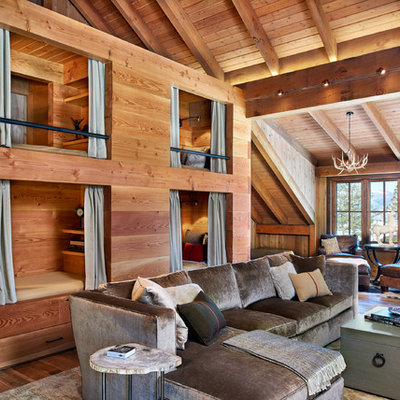 Mid-sized mountain style medium tone wood floor family room photo in Denver with brown walls, a standard fireplace, a stone fireplace and a media wall