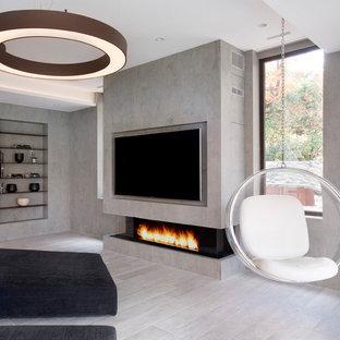Réalisation d'une salle de séjour minimaliste de taille moyenne et fermée avec salle de jeu, un mur gris, un sol en carrelage de porcelaine, une cheminée ribbon, un manteau de cheminée en pierre, un téléviseur encastré et un sol gris.