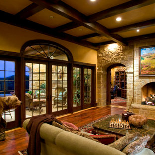 Family room - large mediterranean open concept dark wood floor family room idea in Dallas with beige walls, a two-sided fireplace, a stone fireplace and no tv