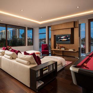 Modelo de sala de juegos en casa actual, grande, sin chimenea, con paredes blancas, suelo de madera oscura, suelo marrón y pared multimedia