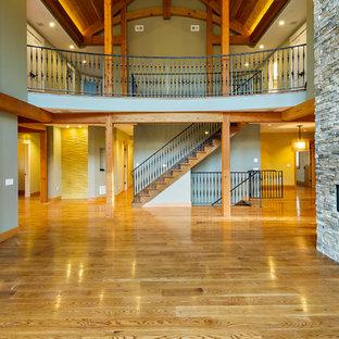 ボルチモアの大きいトラディショナルスタイルのおしゃれなファミリールーム (グレーの壁、濃色無垢フローリング、横長型暖炉、石材の暖炉まわり、テレビなし、茶色い床) の写真