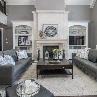 Diseño de sala de estar tipo loft, clásica renovada, grande, con paredes grises, suelo de madera oscura, chimenea tradicional, marco de chimenea de piedra y pared multimedia