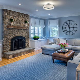 Large transitional enclosed medium tone wood floor family room photo in New York with blue walls, a standard fireplace, a stone fireplace and a wall-mounted tv