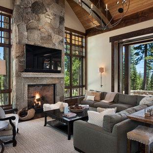 Diseño de sala de estar abierta, rural, grande, con paredes blancas, suelo de madera oscura, chimenea tradicional, marco de chimenea de piedra y televisor colgado en la pared