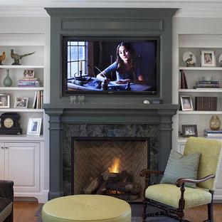 На фото: гостиные комнаты в классическом стиле с серыми стенами, паркетным полом среднего тона, стандартным камином, телевизором на стене и фасадом камина из дерева