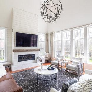 トロントの大きいトランジショナルスタイルのおしゃれなファミリールーム (無垢フローリング、木材の暖炉まわり、壁掛け型テレビ、白い壁、横長型暖炉、茶色い床) の写真