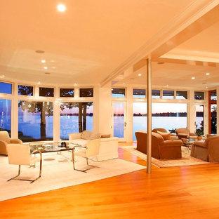 ニューヨークの広いビーチスタイルのおしゃれなオープンリビング (白い壁、無垢フローリング、横長型暖炉、テレビなし) の写真