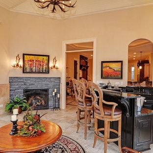 Exemple d'une salle de séjour chic avec un bar de salon, un mur beige, une cheminée d'angle, un manteau de cheminée en pierre et un téléviseur fixé au mur.