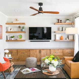 Modelo de sala de estar con biblioteca clásica renovada, sin chimenea, con paredes grises y suelo de madera clara