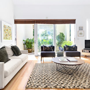 Inspiration for a transitional family room in Melbourne with white walls, light hardwood floors, a freestanding tv and beige floor.