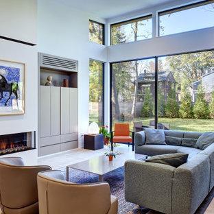 フィラデルフィアの広いコンテンポラリースタイルのおしゃれなオープンリビング (白い壁、コンクリートの床、コーナー設置型暖炉、コンクリートの暖炉まわり、内蔵型テレビ、グレーの床) の写真