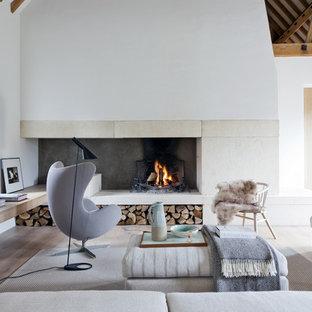 Esempio di un grande soggiorno design chiuso con pareti bianche, parquet chiaro, camino classico, cornice del camino in pietra e nessuna TV