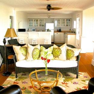 ハワイの中サイズのトロピカルスタイルのおしゃれな独立型ファミリールーム (白い壁、無垢フローリング、茶色い床) の写真
