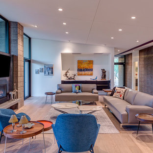 This is an example of a midcentury open concept family room in Phoenix with light hardwood floors, a metal fireplace surround, a wall-mounted tv, white walls, a ribbon fireplace and beige floor.