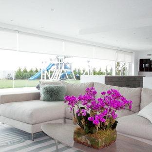 ニューヨークの大きいコンテンポラリースタイルのおしゃれなファミリールーム (白い壁、磁器タイルの床、両方向型暖炉、レンガの暖炉まわり、テレビなし) の写真