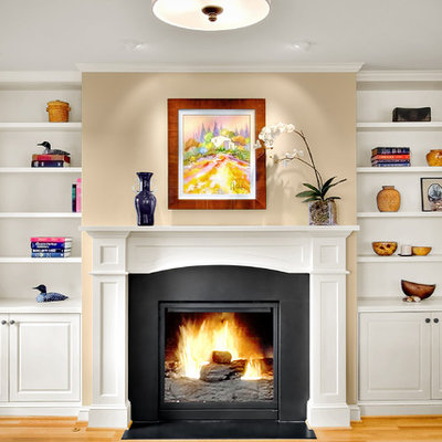 Inspiration for a timeless light wood floor family room remodel in Seattle with beige walls, a standard fireplace and no tv