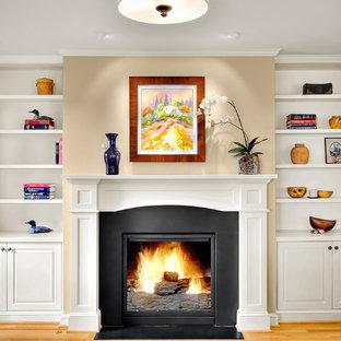 Foto de sala de estar clásica, sin televisor, con paredes beige, suelo de madera clara y chimenea tradicional