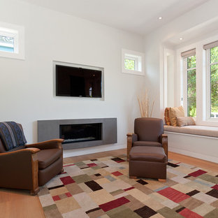 Inspiration for a contemporary enclosed medium tone wood floor family room remodel in Vancouver with white walls, a ribbon fireplace and a wall-mounted tv
