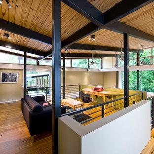Пример оригинального дизайна: двухуровневая гостиная комната в современном стиле с бежевыми стенами и паркетным полом среднего тона