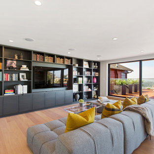 Family room library - large contemporary open concept light wood floor and beige floor family room library idea in San Francisco with white walls and a wall-mounted tv