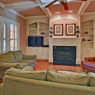 ローリーの中サイズのトラディショナルスタイルのおしゃれな独立型ファミリールーム (ベージュの壁、無垢フローリング、標準型暖炉、木材の暖炉まわり、据え置き型テレビ、ピンクの床) の写真
