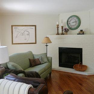 ワシントンD.C.の小さいカントリー風おしゃれなファミリールーム (ベージュの壁、無垢フローリング、コーナー設置型暖炉、レンガの暖炉まわり、内蔵型テレビ) の写真