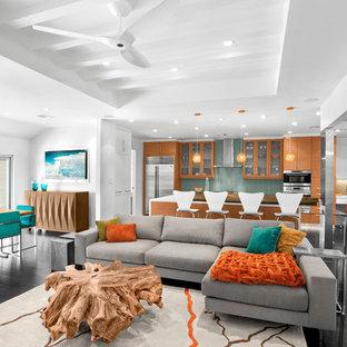 Exemple d'une salle de séjour rétro de taille moyenne et ouverte avec un mur blanc, un sol en bois foncé, aucune cheminée, un téléviseur fixé au mur et un sol marron.