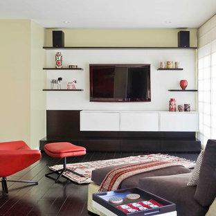 Idées déco pour une salle de séjour rétro avec un sol en bois foncé, un téléviseur fixé au mur et un mur vert.