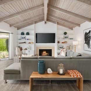 他の地域の大きいビーチスタイルのおしゃれなファミリールーム (白い壁、標準型暖炉、壁掛け型テレビ、ベージュの床) の写真