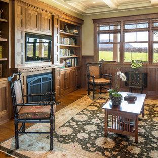 Idées déco pour une salle de séjour avec une bibliothèque ou un coin lecture craftsman de taille moyenne et fermée avec un sol en bois brun, une cheminée standard, un manteau de cheminée en bois, un téléviseur fixé au mur et un mur beige.