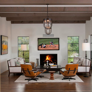 Tuscan enclosed family room photo in San Diego with a standard fireplace and a wall-mounted tv