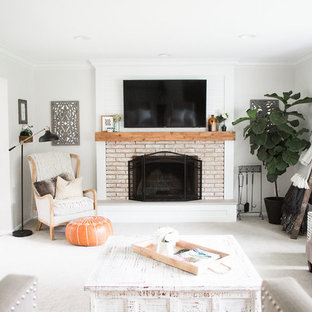 Example of a large cottage chic enclosed carpeted and gray floor family room design in Minneapolis with a standard fireplace, a wall-mounted tv, gray walls and a brick fireplace