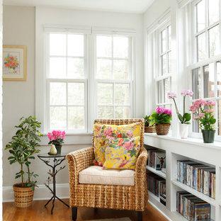 Foto de sala de estar con biblioteca abierta, tradicional, pequeña, sin televisor, con paredes beige, suelo de madera en tonos medios y suelo marrón