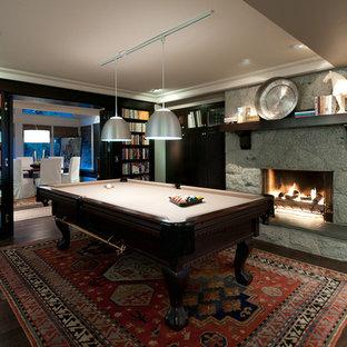 Imagen de sala de juegos en casa contemporánea, sin televisor, con suelo de madera oscura, chimenea tradicional y marco de chimenea de piedra