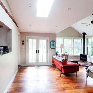 Ejemplo de sala de estar abierta, de estilo americano, de tamaño medio, con paredes beige, suelo de madera clara, estufa de leña, marco de chimenea de metal y suelo marrón