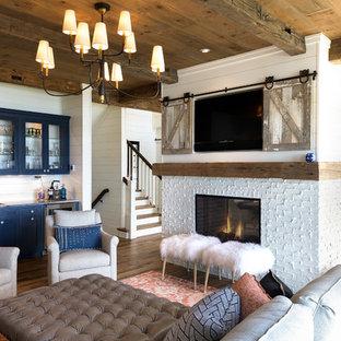 Foto de sala de estar con barra de bar marinera, grande, con paredes blancas, chimenea de doble cara, marco de chimenea de ladrillo, suelo marrón, suelo de madera oscura y televisor retractable