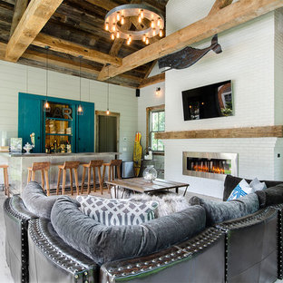 Foto de sala de estar abierta, costera, pequeña, con paredes blancas, suelo de madera clara, chimenea tradicional y marco de chimenea de ladrillo