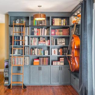 Foto di un grande soggiorno classico aperto con libreria, pareti blu e pavimento in legno massello medio