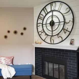 ロサンゼルスの小さいビーチスタイルのおしゃれなファミリールーム (ベージュの壁、クッションフロア、標準型暖炉、石材の暖炉まわり、据え置き型テレビ、茶色い床) の写真