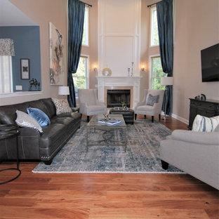 ニューヨークの大きいトラディショナルスタイルのおしゃれなオープンリビング (ベージュの壁、無垢フローリング、標準型暖炉、石材の暖炉まわり、壁掛け型テレビ、オレンジの床) の写真