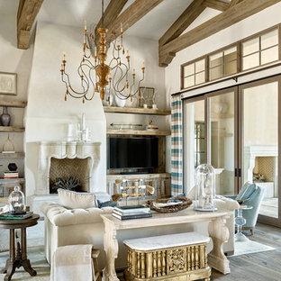 Foto de sala de estar mediterránea con paredes beige, suelo de madera en tonos medios, chimenea tradicional y pared multimedia