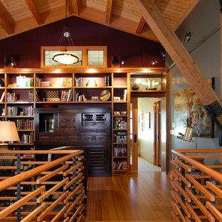 Réalisation d'une salle de séjour avec une bibliothèque ou un coin lecture chalet avec un mur gris et un sol marron.
