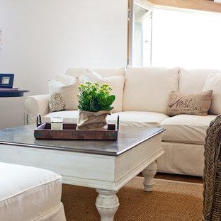 オマハの大きいシャビーシック調のおしゃれなファミリールーム (ライブラリー、白い壁、無垢フローリング、標準型暖炉、石材の暖炉まわり、茶色い床) の写真