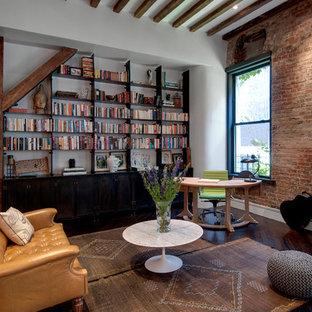 Foto di un soggiorno industriale con libreria, pareti bianche, parquet scuro e nessuna TV