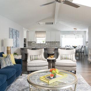 ダラスの大きいトラディショナルスタイルのおしゃれなファミリールーム (グレーの壁、無垢フローリング、標準型暖炉、タイルの暖炉まわり、埋込式メディアウォール、茶色い床) の写真