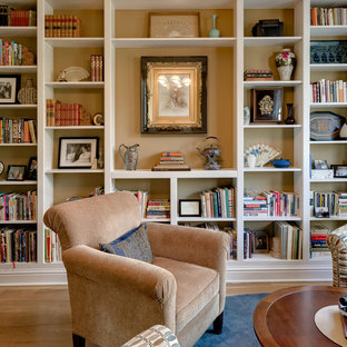 Example of a mid-sized transitional open concept light wood floor family room library design in Columbus with beige walls, no fireplace and no tv