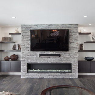 Inspiration for a mid-sized modern open concept dark wood floor game room remodel in Orange County with gray walls, a hanging fireplace, a stone fireplace and a media wall