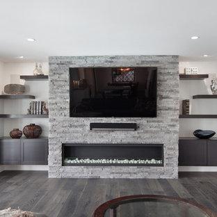 Imagen de sala de juegos en casa abierta, moderna, de tamaño medio, con paredes grises, suelo de madera oscura, chimeneas suspendidas, marco de chimenea de piedra y pared multimedia