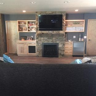 Imagen de sala de estar abierta, campestre, grande, con paredes azules, suelo de madera clara, chimenea tradicional, marco de chimenea de metal y televisor colgado en la pared